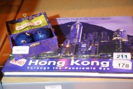 Pair of oriental iron directional balls and a photographic panoramic view of Hong Kong hardback book