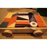 A wooden pull along trolley containing coloured childrens building blocks. Not available for in-