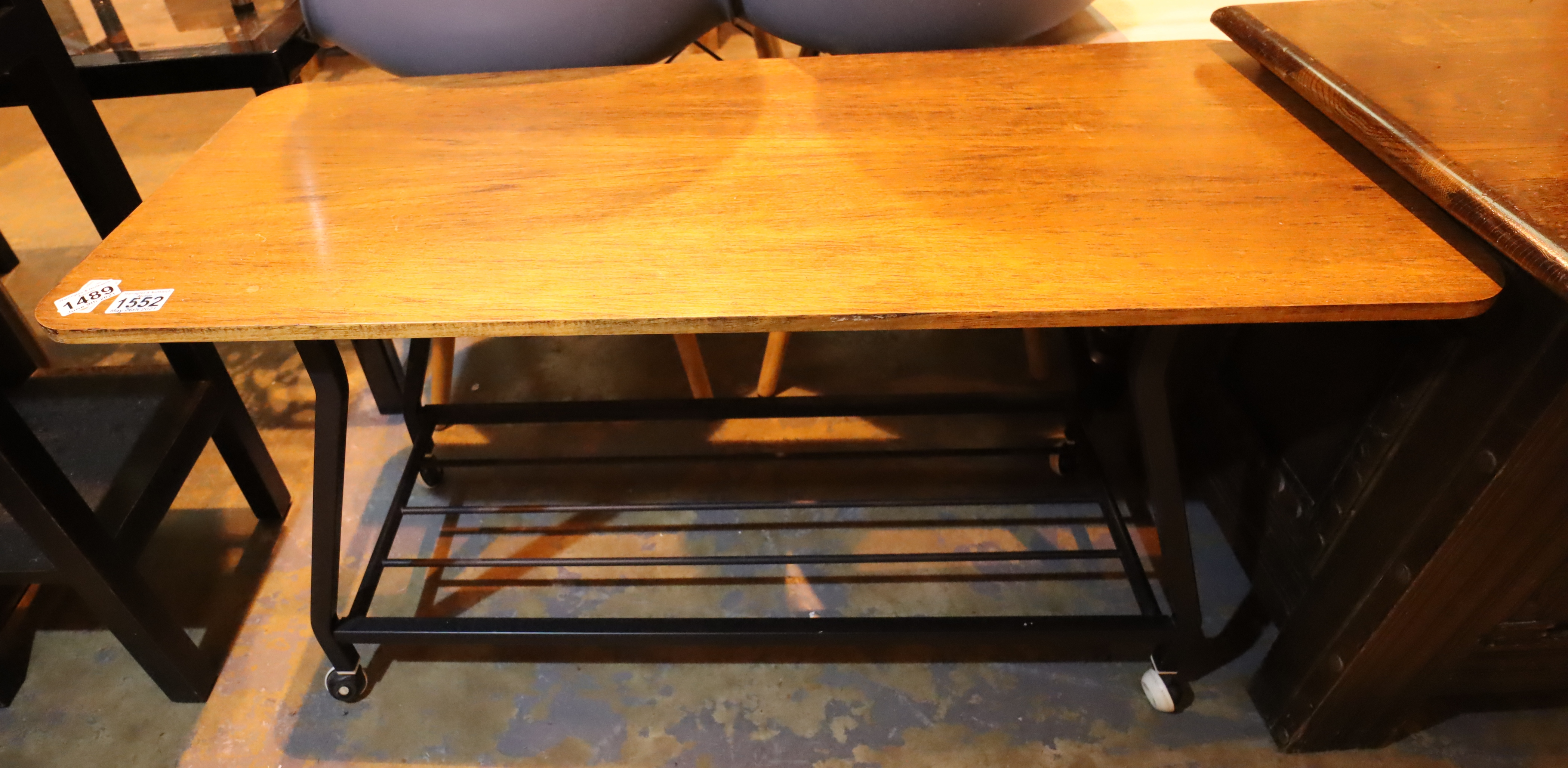 A retro metal framed teak topped coffee table on castor supports. Not available for in-house P&P,