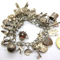 925 silver charm bracelet with padlock clasp and 29 charms, combined 91g. P&P Group 1 (£14+VAT for