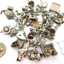 Silver charm bracelet with twenty three charms, combined 139g. P&P Group 1 (£14+VAT for the first