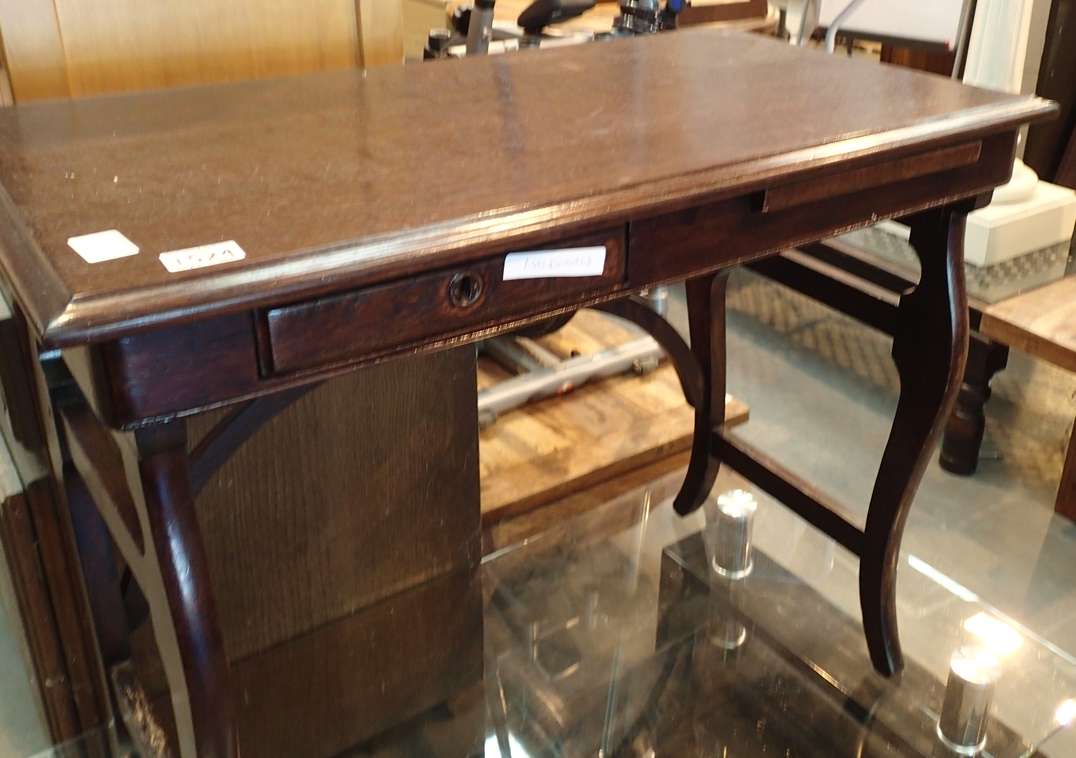 Good quality single drawer and sliding rest mahogany table and a glass TV stand. Not available for