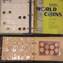 A small collection of UK and world coins, housed in two part-filled albums, together with empty coin