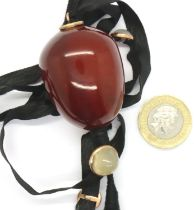Large cherry amber pendant on a fabric strap with moonstone cabochons, amber 40 x 30 mm, combined