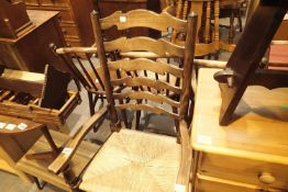 Large antique oak ladder back carver chair with rush seat, H: 110 cm. Not available for in-house P&