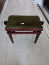 A modern adjusting piano stool upholstered in green