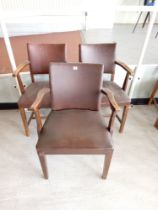 Three faux leather backed elbow chairs