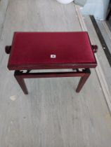 A modern adjusting piano stool upholstered in Red