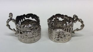 A pair of unusual pierced silver shot glass holder