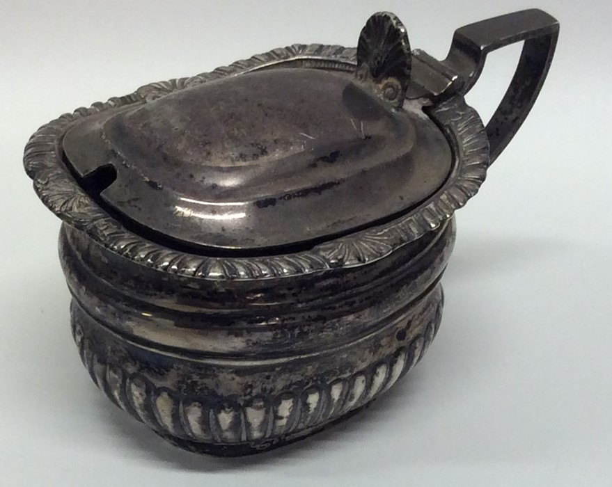 A heavy Edwardian silver mustard with hinged lid.