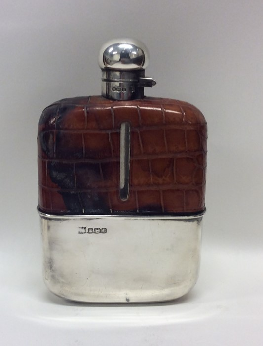 A large silver and glass hip flask with crocodile