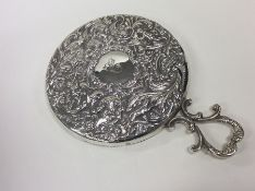 A good embossed silver mirror decorated with cheru