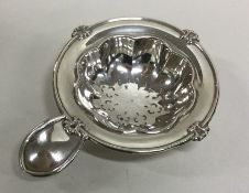 An attractive silver tea strainer with plain thumb