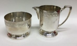 A silver plated cream jug and sugar bowl. Est. £10