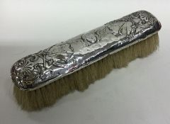 A silver clothes brush decorated with winged infan
