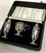 A heavy silver cased three piece silver cruet set.