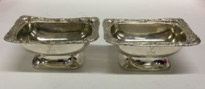 A pair of Georgian silver salts with crested sides