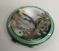 A circular silver and enamelled compact decorated