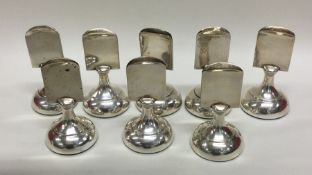 A good set of eight silver menu holders of circula
