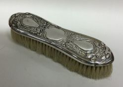 A chased silver clothes brush mounted with wheatsh