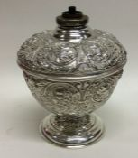 A rare Victorian silver embossed oil lamp attracti