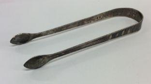 A pair of Georgian silver bright cut sugar tongs.