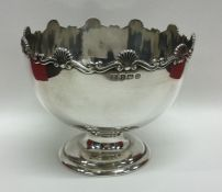 A circular silver bowl with shell border to sweepi