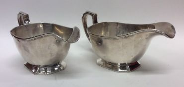 A pair of heavy silver sauce boats with cut corner