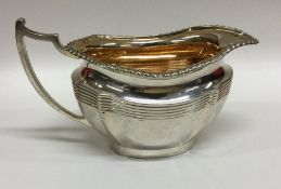 A heavy silver shaped cream jug with gadroon rim.