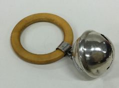 A circular silver rattle together with wooden teet