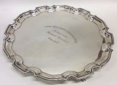 A large circular silver salver on three tapering s