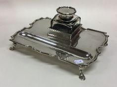 An Edwardian silver single bottle inkstand with sh