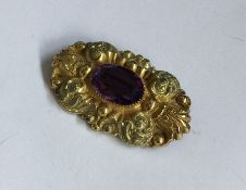 An amethyst mounted brooch decorated with scrolls