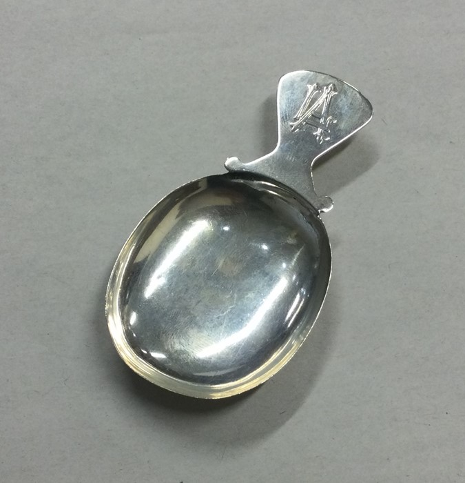 A Continental silver caddy spoon with shaped rim.