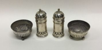 A pair of silver salts together with peppers. Vari