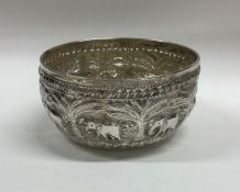 An Indian silver bowl chased with scrolls and flow