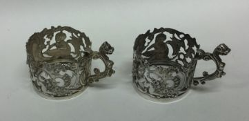 A pair of pierced silver cup holders decorated wit