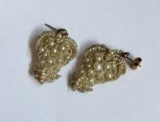A pair of gold mounted seed pearl drop earrings. A
