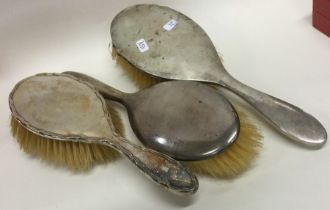 A group of three silver mounted hairbrushes. Est.
