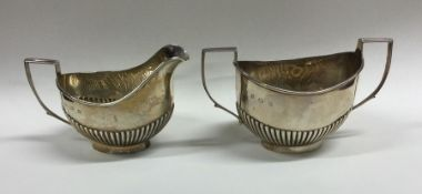 A silver half fluted cream jug together with match