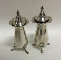 A pair of Edwardian silver peppers of typical form