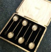 A cased set of six silver bean top coffee spoons.