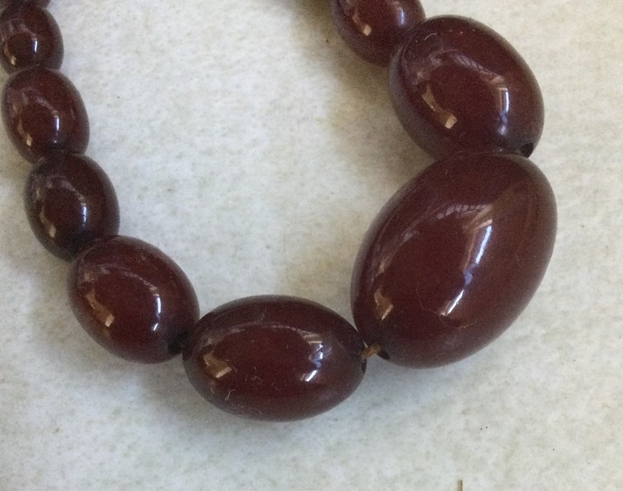 A tapering string of red amber beads. 43 grams. Es - Image 2 of 2