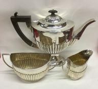 A large silver three piece half fluted tea service