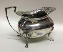 A heavy Edwardian silver cream jug with card cut r