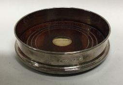 A silver and gold mounted wine coaster with mahoga