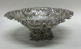 A large circular silver bonbon dish with floral de