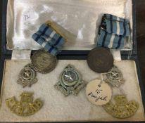 A box containing cap badges etc. Est. £10 - £20.