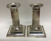 A pair of Edwardian silver candlesticks with flute