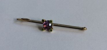 An amethyst and gold bar brooch in claw mount. App